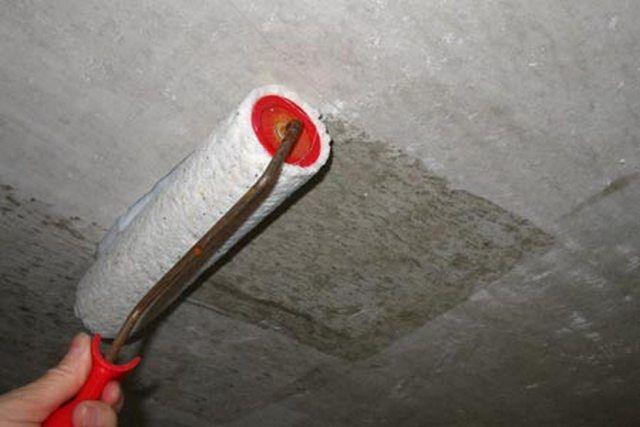 Нанесение грунтовки на поверхность потолка
