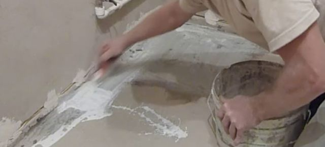 Процесс грунтования пола с помощью кисти