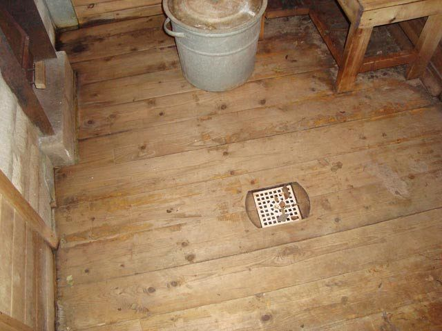 Сливная решетка на деревянном полу