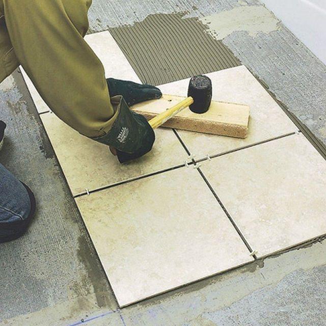 Подгонка плоскости плитки с помощью резинового молотка