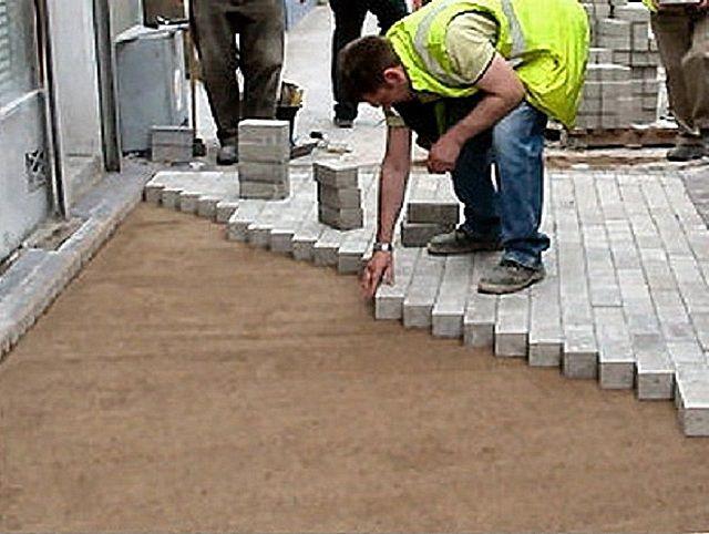 Чтобы не повредить выровненный слой песка, укладку тротуарной плитки лучше вести от себя