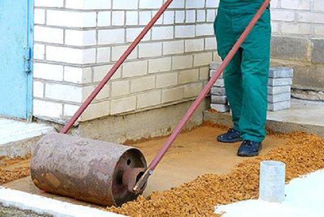 Уплотнение песчаного слоя ручным катком