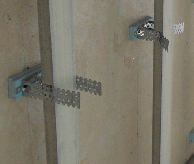 Брусья обрешетки закреплены в подвесах. Те, в свою очередь, отделены от стены противовибрационными подкладками
