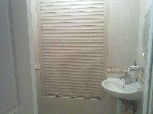 Скрыть коммуникации поможет декоративная фальшь-стена, например, со шторкой в виде жалюзи