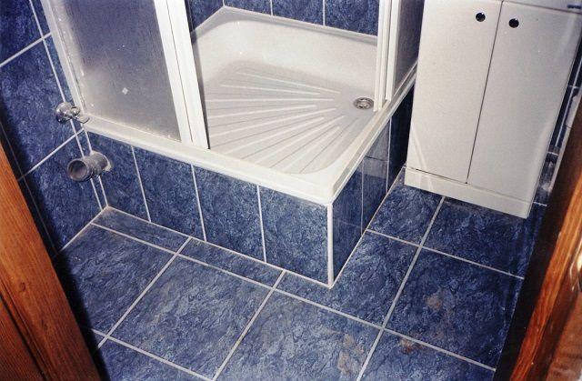 Неглубокий поддон установлен на облицованный плиткой подиум
