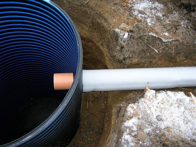 Сточная труба в утеплительном кожухе отведена выгребную яму