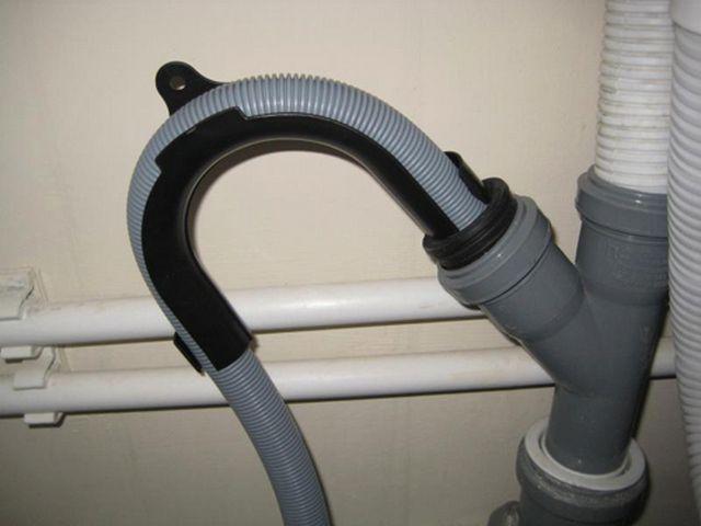«Косой» тройник и установленный в него дренажный шланг с уплотнением резиновой ребристой муфтой. Обеспечение изгиба достигается с помощью специальной вставки.