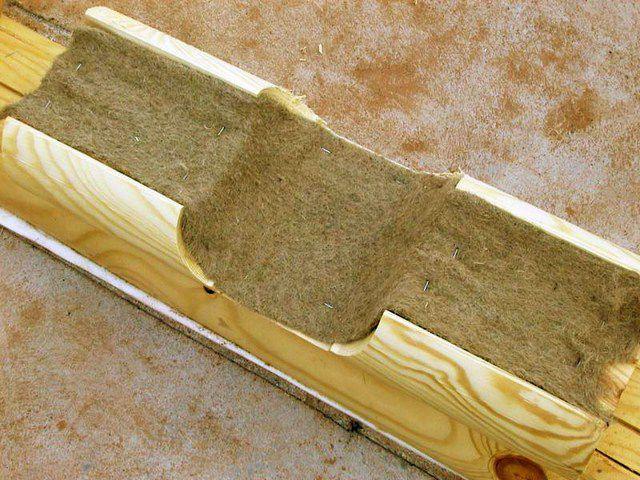 Полоса утеплителя закреплена к брусу скобами степлера