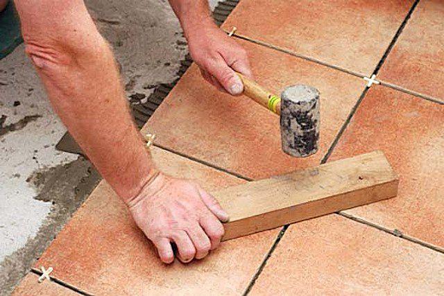 Легкие удары резиновым молотком через деревянный брусок помогут вывести укладываемую плитку на нужный общий уровень.