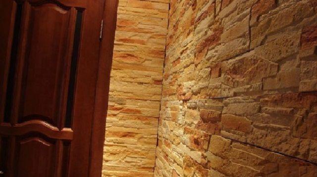 Искусственным камнем отделана вся стена, от пола до потолка