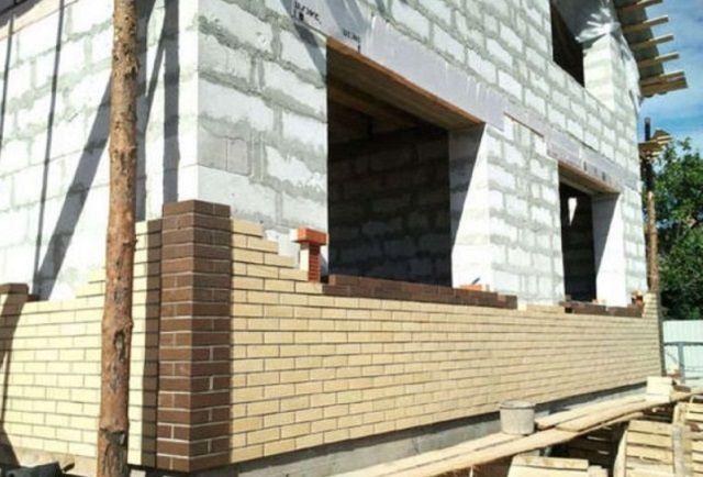 Отделку фасада кирпичом можно проводить практически параллельно с возведением самих стен
