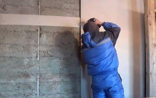 Установка промазанного монтажной пеной листа на стену по маякам-площадкам