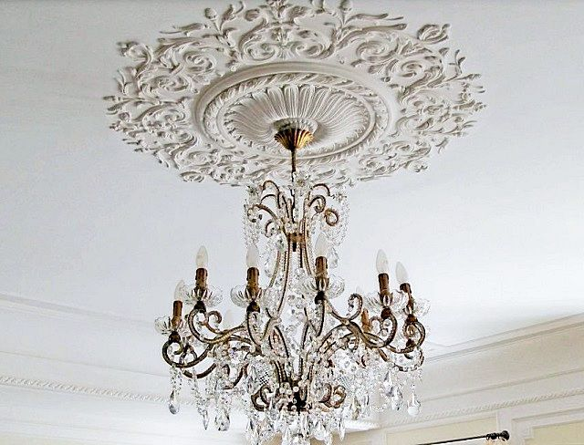 В стиле «барокко», помимо линейных молдингов, обязательно напрашивается декоративная розетка под люстру, строго по центру потолочной поверхности