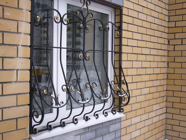 Глухая решетка на окне частного дома.
