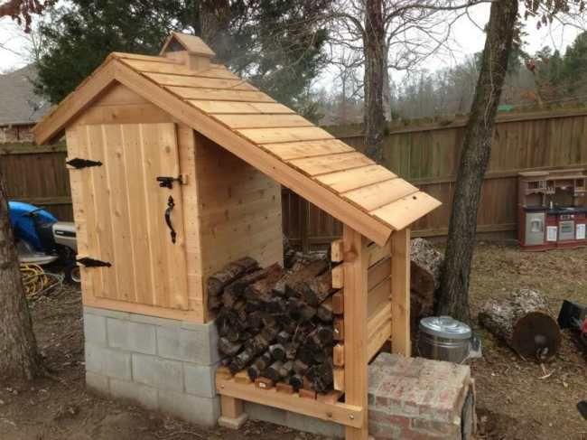 Интересный вариант деревянной коптильни, совмещённой с навесом для сушки и хранения дров