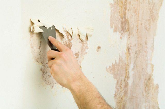 Очистка стены с помощью шпателя, применяемого в роли скребка