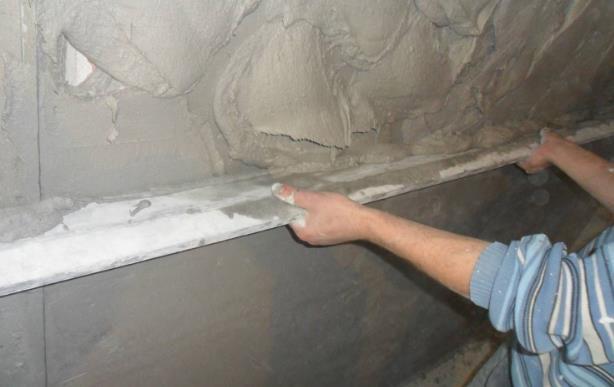 Разравнивание нанесенного на стену штукатурного раствора правилом