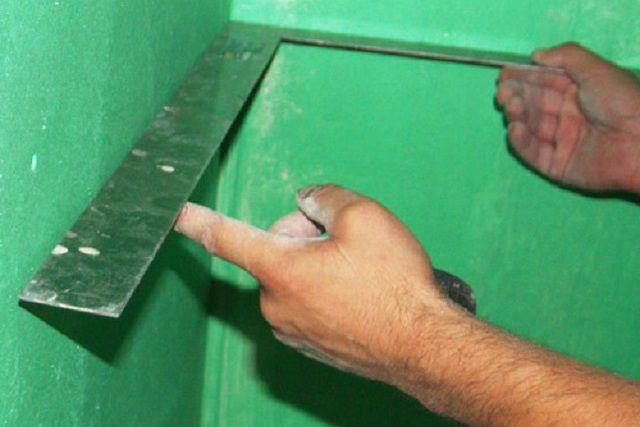 Проверка перпендикулярности стен с помощью угольника.