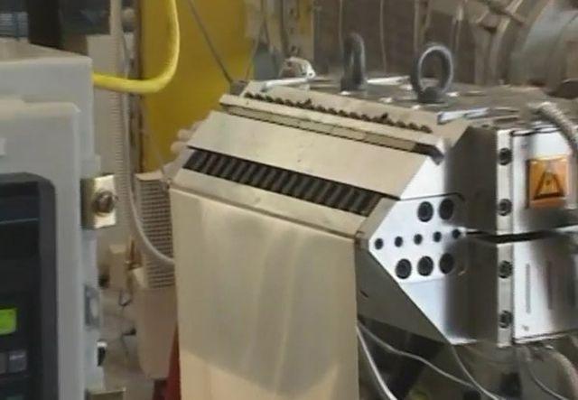 Фильера с выходящим из нее полотном ПВХ, которая является заготовкой для сайдинга