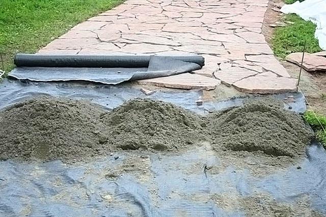 Процесс мощения дорожки плитками натурального камня – хорошо виден слой геоткани