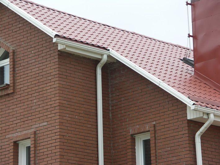 Фото: металлочерепица Металл Профиль на крыше здания, смонтированная водосточная система