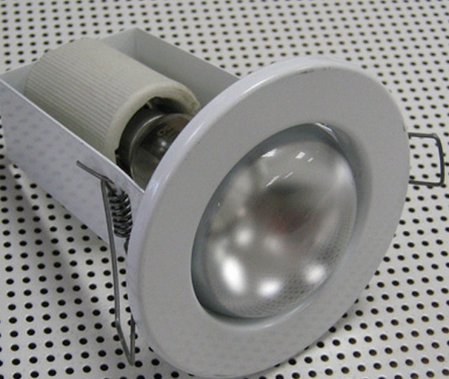 Типичная схема фиксации точечных светильников в прорезанных для них проемах – за счет пружинных «ушек» по бокам