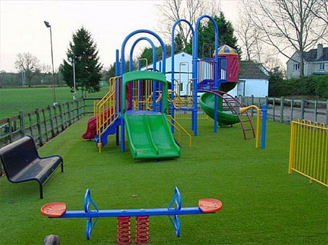 Детская игровая площадка, застеленная искусственным газоном