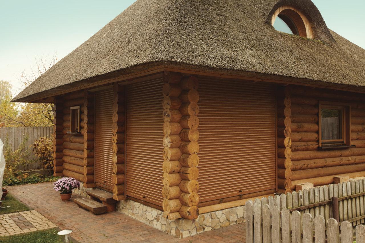 Гармоничное сочетание роллет и бревенчатых стен дома