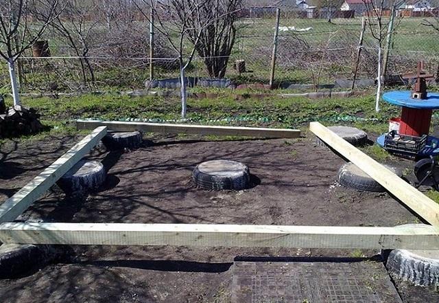 В качестве столбов фундамента под беседку применены старые автомобильные покрышки, которые стали опалубкой для заливки бетона