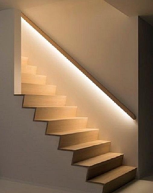 Светодиодная лента, наклеенная под поручни, выгодно декорирует область лестницы, давая мягкий свет на ступени, а также оригинально разделяя стену на более светлый и темный участки.