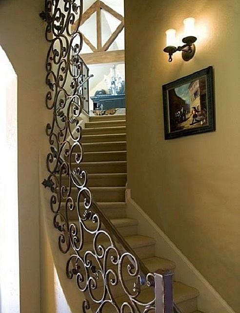 Лестничный марш с ограждением, выполненным из кованных металлических деталей. Такому классическому стилю больше подойдут настенные светильники по типу бра