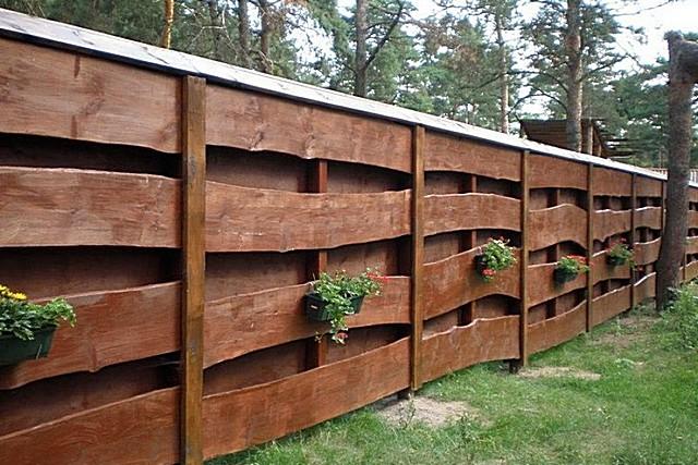 Очень оригинальный и симпатичный забор вполне можно соорудить даже из не обрезной доски или горбыля