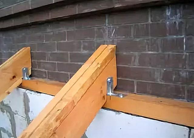 Вариант узла крепления стропила односкатной крыши пристройки к стене основного здания