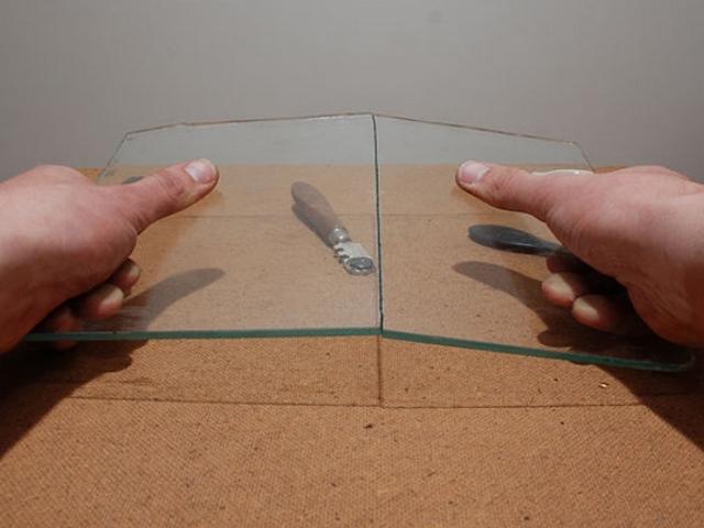 Второй шаг – стекло должно ровно обломиться по нанесенной бороздке (это показан пример, а так в ходе работы рукавицами пренебрегать не стоит).