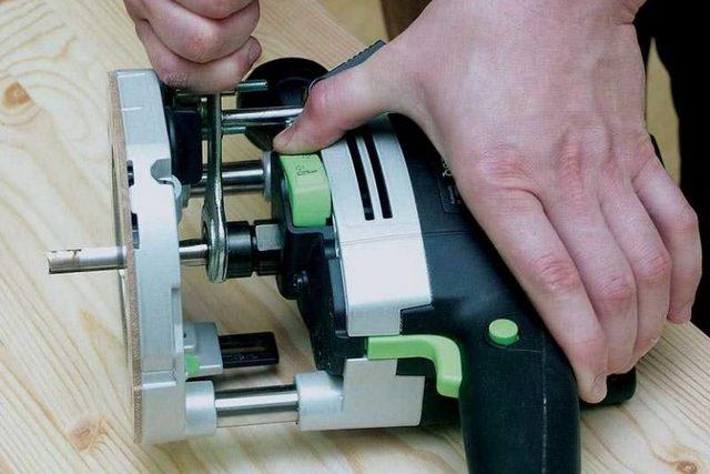 Установка фрезы в цангу ручного фрезера — шпиндель стопорится специальной кнопкой, а затем производится затяжка патрона рожковым ключом