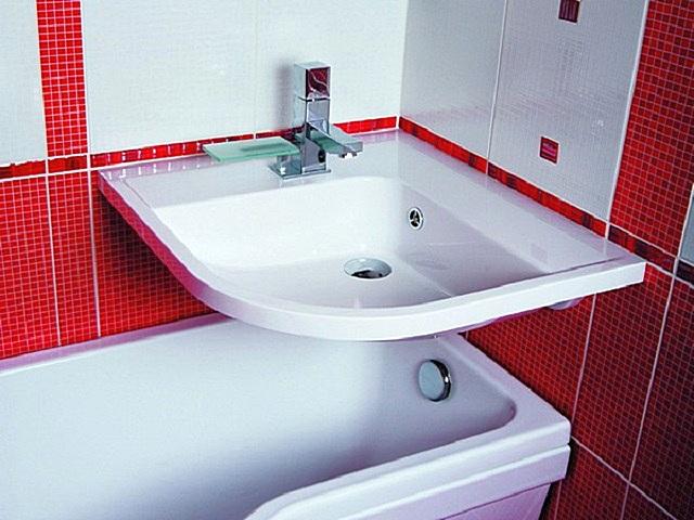 Угловая раковина, закрепленная над ванной, значительно сэкономит площадь помещения.