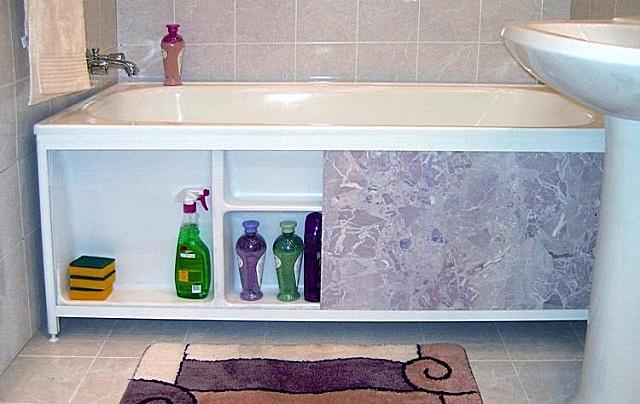 Шкафчик с дверкой расположился под ванной. Подобные конструкции можно приобрести, а умелый хозяин в состоянии изготовить и самостоятельно.