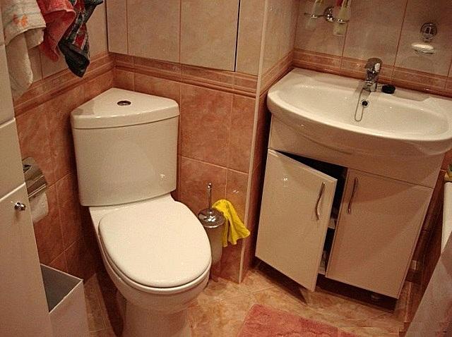 Угловой унитаз в маленькой ванной.