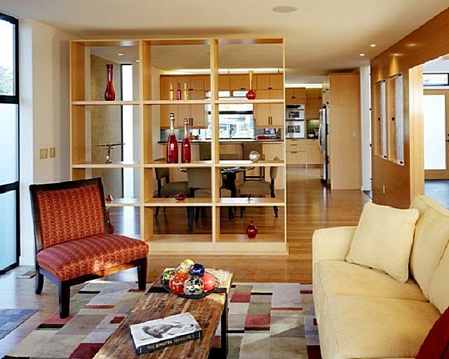 В качестве перегородки используется «прозрачный» стеллаж, который может как оставляться пустым, так и предназначаться для расстановки традиционных предметов интерьера или кухни, или гостиной