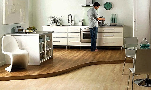 Фигурный невысокий подиум явно выделяет кухонную зону из объединенного помещения