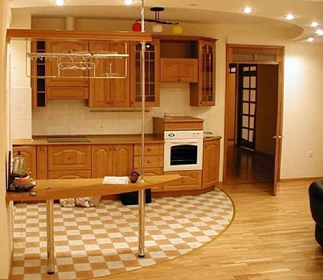 Плитка в зоне кухни и ламинат или паркет – в гостиной. Важно, чтобы переход был гармоничным, соответствующим общему дизайну объединенного помещения.