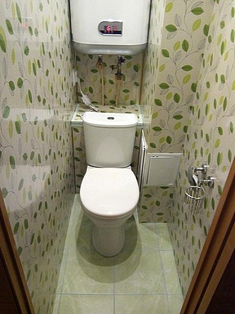 Аккуратно и без особых излишеств – отделка стен туалета пластиковыми панелями со светлым растительным рисунком.