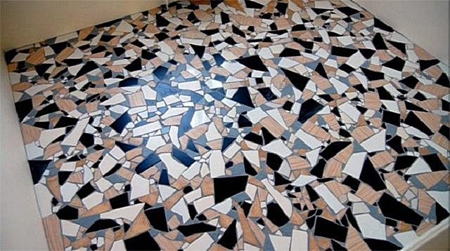 Разноцветные фрагменты керамической плитки, уложенные в хаотичном порядке.