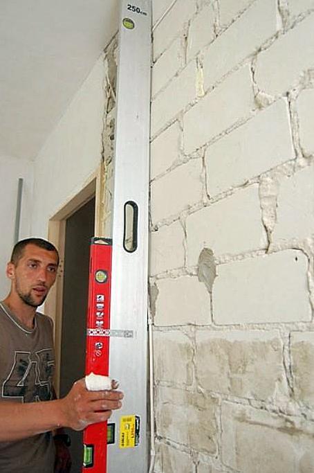 Контроль вертикальности стены с помощью длинного правила и строительного уровня