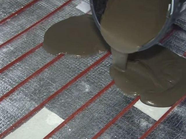 Подготовленный плиточный клей выливается на поверхность пола и распределяется по ней на определенном участке для достижения требуемой толщины.
