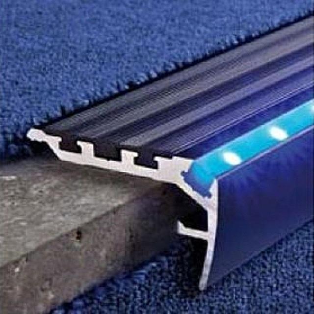 Уголки, оснащенные противоскользящей эластичной полосой. Они специально предназначены для крепления ковровых накладок на ступени. В данном случае показан вариант, оснащенный еще и подсветкой.