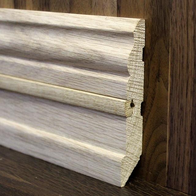 Деревянный плинтус с пазом для проведения фиксации к стене на саморезы. После установки паз закрывается вставкой.