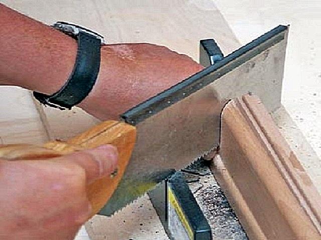 Отпиливание края плинтуса под углом с помощью стусла и обушковой пилы