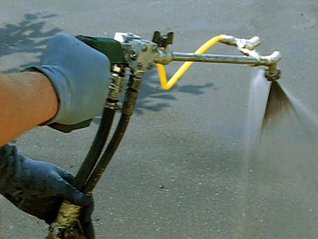 Нанесение жидкой резины с помощью специального двухканального распылителя. Хорошо видны два факела, которые смешиваются непосредственно на обрабатываемой поверхности.