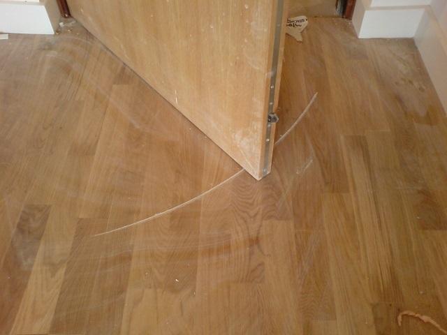 Ламинат, поврежденный дверным полотном.